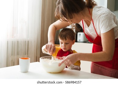 Mom with her little son cooking preparing the dough, bake cookies in the kitchen at home. Casual lifestyle photo series in real life interior