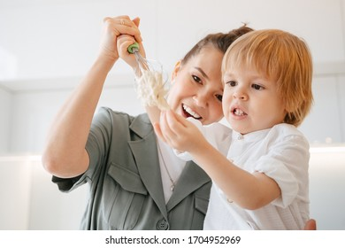 Mom with her son prepares the dough in a bright kitchen. A child with mom plays with sticky dough. Dough sticks to hands and a whisk.