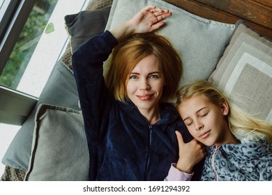 Mom with her teenage daughter are lying on the bed. The relationship of mother and child.