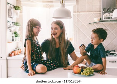 Mom with her two children sitting on the kitchen table and eating fruits together. Mother with daughter and toddler son having breakfast at home. Happy lifestyle family moments.