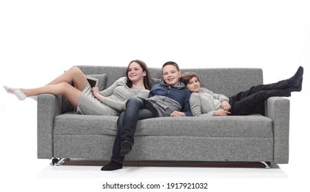 mom and her two sons relax sitting on the couch.
