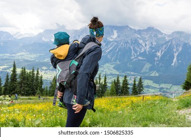Mom hiking with her baby in a kangaroo backpack or in sling, austria alps
