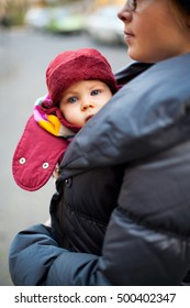 Mom holding baby in sling bundled up in coat and hat outside.