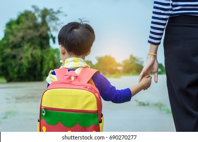 Mom holding hand of little son with backpack outdoors, back to school,looking back home with floods.
