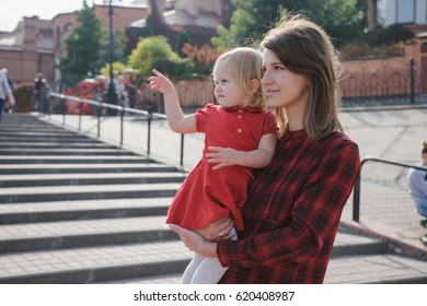 Mom holding her little daughter in red dress. They looking and pointing away