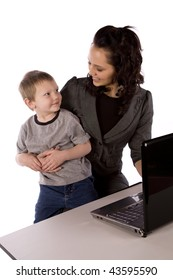A mom holding her son while trying to work on her computer, smiling at eachother.