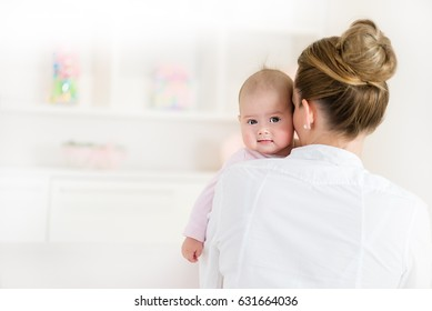 Mom holding little baby girl, baby looking at camera.Copy space
