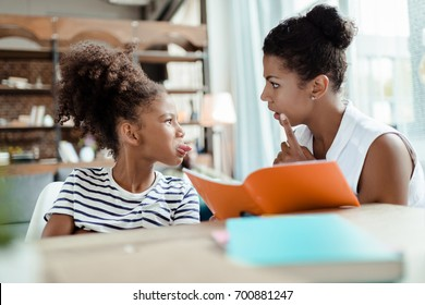 Mom holding a notebook and scolding her daughter for sticking her tongue out