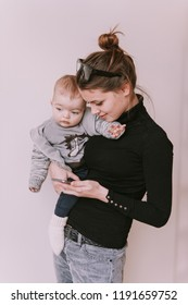 Mom holding son and looking onto the mobile phone. Mother and baby boy are looking to play on  smart phone. Family, working mum