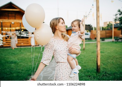 Mom holds a baby in her arms and air balloons. Birthday party
