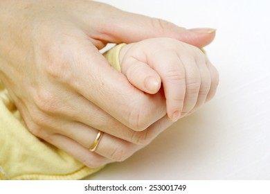 Mom holds child's hand, close-up