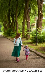 Mom holds daughter's hand walking with her in the park after rain