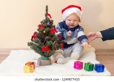 Mom holds the hand of a disgruntled funny kid in a Santa hat