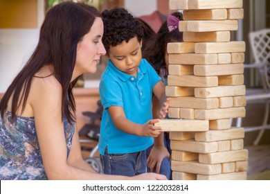 Mom holds her breath as her little boy carefully removes a block from the jumbling wood tower. The wooden large size jumbling tower  holds steady while the boy keeps it in place with the other hand.