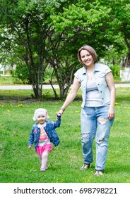 Mom holds her child by the hand, walking in the park, cheerful. Beautiful people, blondes, blue-eyed.