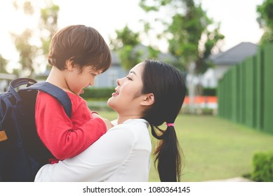 Mom hug and carry her son. Preparing to send her children back to school in morning. Education and Back to school concept. Happy family and Loving of people theme