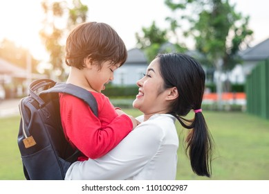 Mom hug and carry her son. Preparing to send her children back to school in morning. Mother playing with kids. Education and Back to school concept. Happy family and Loving of people theme