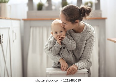 Mom hugs baby son, daylight in real interior. concept of motherhood and affection