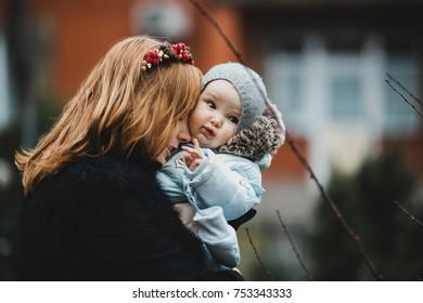 Mom hugs her child tender standing outside