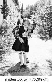 Mom hugs her little daughter , she is an elementary school student.
