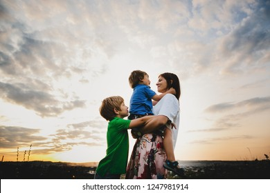 Mom hugs with her two little sons tender standing in the rays of warm evening summer sun