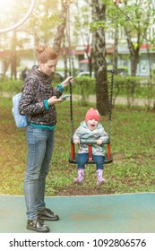 Mom, keen on the phone, swings the child on a swing