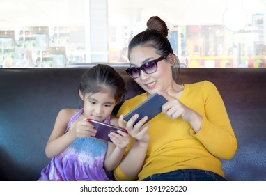 mom and kid addict mobile in digital behavior. people lost face to face relation with digital equipment