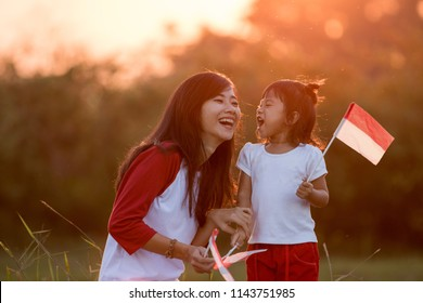 mom and kid having fun in the field with flag. indonesia independence day celebration concept