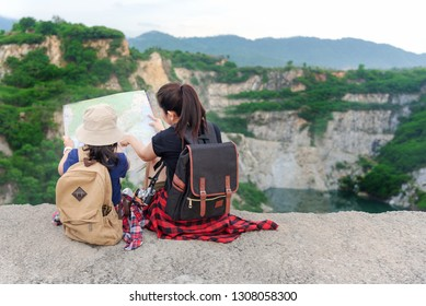 Mom and kid holding maps and travel backpacks sitting victorious facing on the outdoors adventure grand canyon for education nature. Travel Concept