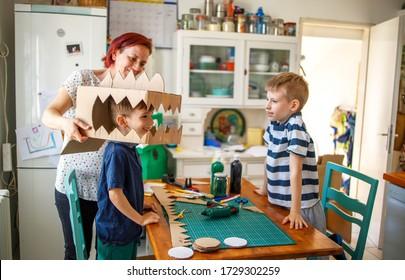 Mom and kids making a cardboard dinosaur costume