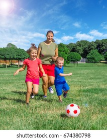 Mom and the kids play football in the park