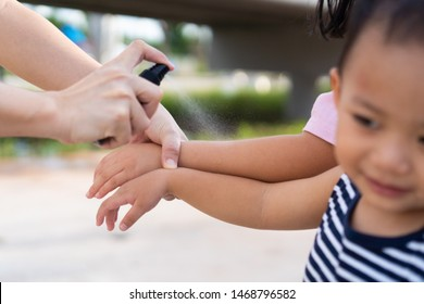 Mom and kids use mosquito spray.Spraying insect repellent on skin outdoor.Mom protect his boy child from mosquitoes bite and itching his leg.Safety first from Mosquito sucking blood on child skin.