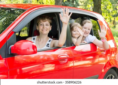 Mom with kids waving from the window of a car