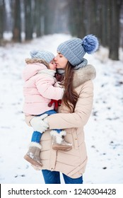 Mom kisses her little daughter gentle to the nose. Stylish young mother playing with her little cute daughter in winter snow park.