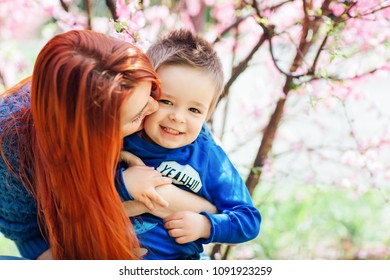 Mom kisses and plays with her son in the park near the almond blossom