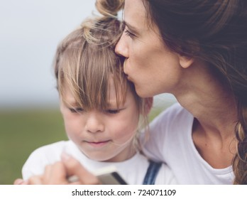 mom kissing preschooler girl. mother and daughter sitting together. older and younger sisters spending time together.