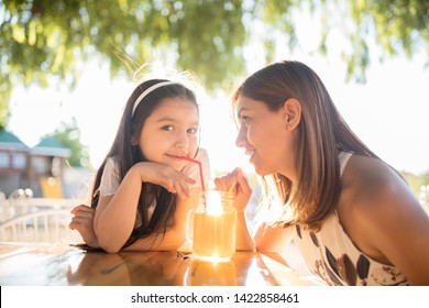 mom and latina daughter drinking happy juice happy women latinas