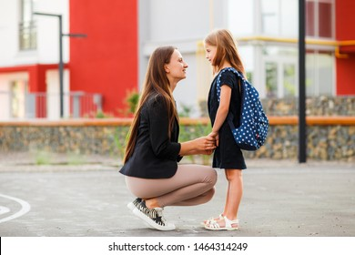 Mom leads her daughter to school. Return to school. Woman and girl with backpack behind the back. Beginning of lessons. First day of fall.