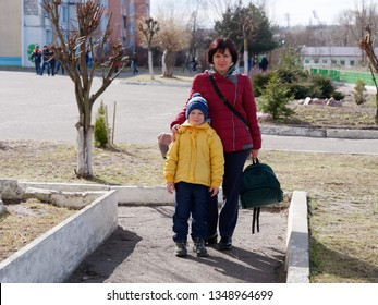 mom leads her son to primary school.