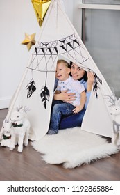 mom and little baby boy hide in a tent or an Indian wigwam and play in the Indians