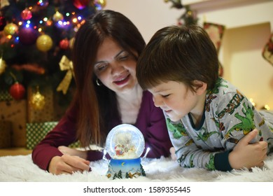 Mom and little boy looking a glass snow ball under a Christmas tree. Mother and son with a snow ball with a New Year