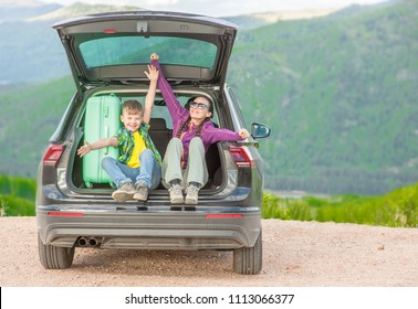 Mom and little boy sitting in hatchback car with mountain background