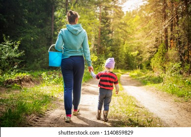 Mom and little daughter go on the road in the autumn forest. The family gather mushrooms and berries in the forest on a sunny day. Spending time outdoors