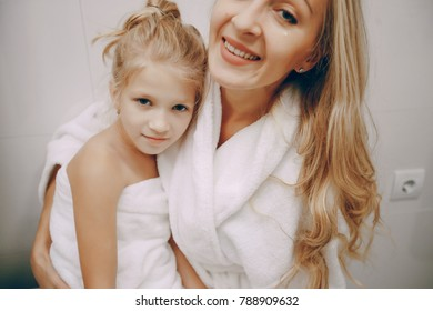 Mom and little daughter at home in the bathroom in a towel