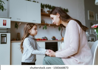 mom with a little daughter in the kitchen. the girl tells something and mom listens carefully to her