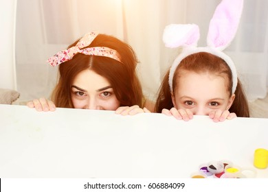 Mom and little daughter look out from under the table. Girl wearing rabbit ears for easter. Easter colored Easter eggs on a table