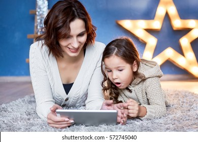 mom and little daughter lying on the floor and playing tablet