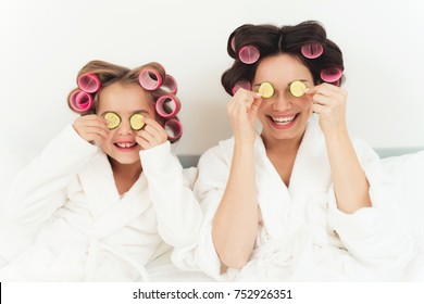 Mom and little daughter are lying on a bed in white coats and holding cucumber slices in their hands. On their heads they have curlers. Nearby lie chocolate sweets. They are very fun.