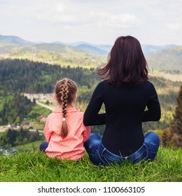 Mom and little daughter are meditating on the top of the mountain. Square. The concept of family, yoga, travel.