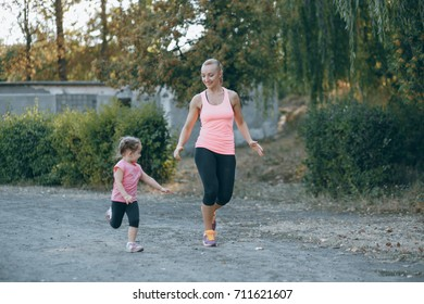 mom and little daughter running in summer park